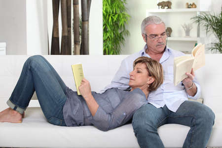Couple reading on white sofa Stock Photo - 14214984