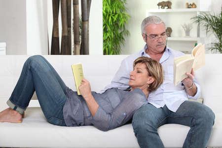 Couple reading on white sofa Stock Photo - 14214984