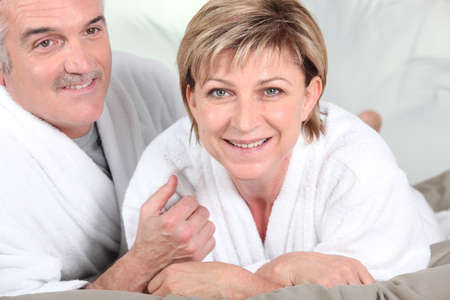 maintained: Mature couple in bed with bathrobe