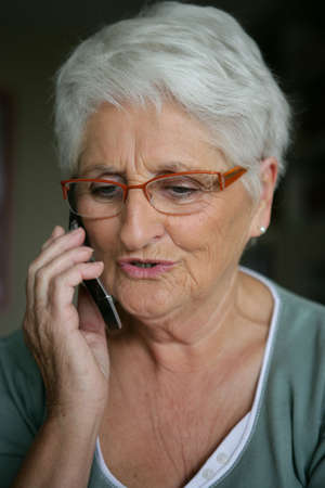 Elderly lady making telephone call photo