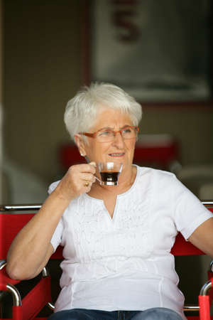 Elderly woman drinking a cup of coffee photo