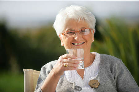 water beautiful: Senior woman with a glass of water Stock Photo