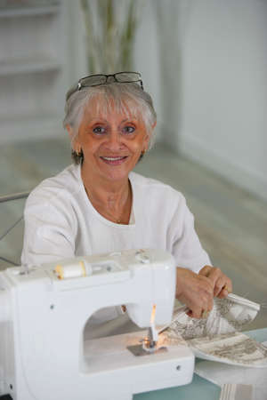 Elderly lady using sewing machine photo
