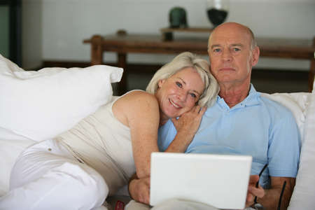 Middle-aged couple in bed with laptop photo