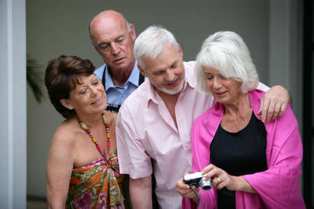 Two elderly couple looking at photos on digital camera photo