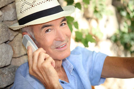 Older man using a cell phone outdoors photo