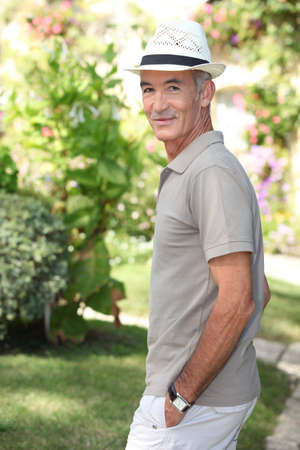 Senior man walking in the garden photo