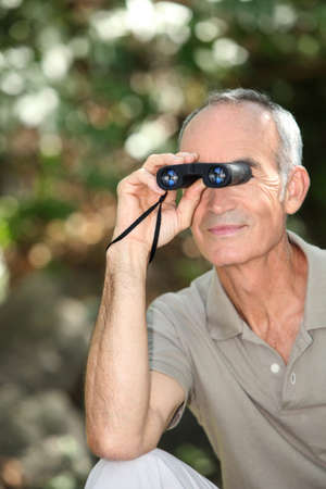 Senior man bird watching with binoculars