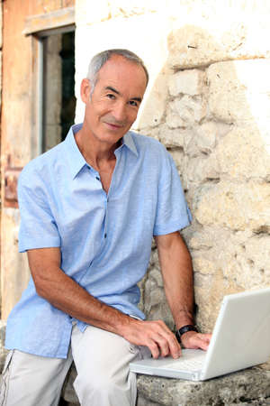 grey haired: Grey haired man sat by stone wall with laptop Stock Photo