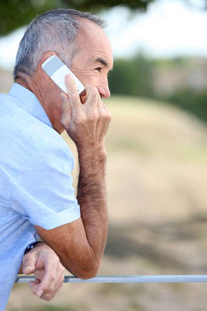 old cell phone: Elderly man talking on his mobile phone outdoors Stock Photo