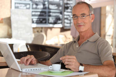 Grey-haired man in coffee shop photo
