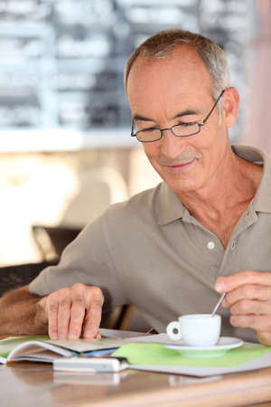 Old man drinking coffee and reading photo