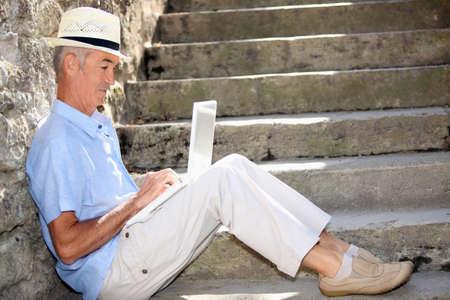 senior gentleman working on laptop outdoors Stock Photo - 14214631