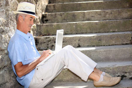 senior gentleman working on laptop outdoors Stock Photo - 14214631