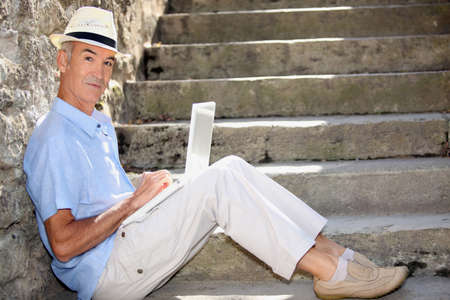 mature man doing computer outside at the foot of stairs photo