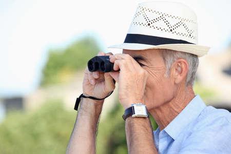 birdwatcher: Old man looking through binoculars Stock Photo