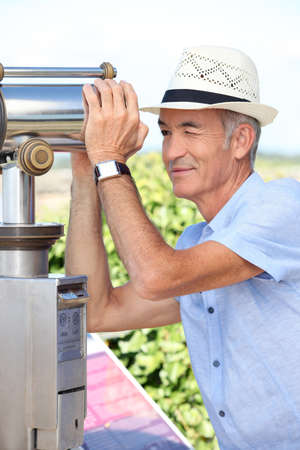 staying in shape: Senior man looking through a telescope