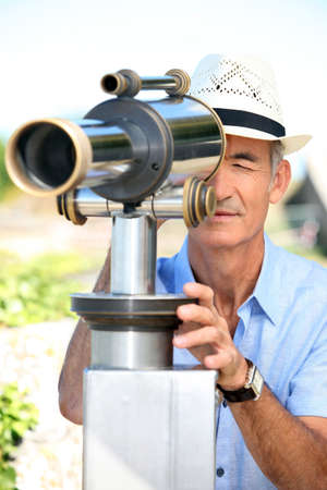 lens unit: Man looking through telescope Stock Photo