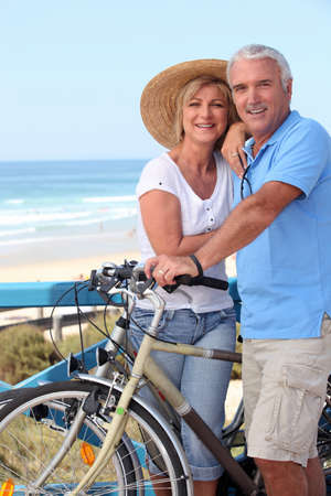 senior exercise: Mature couple with bikes by a beach Stock Photo