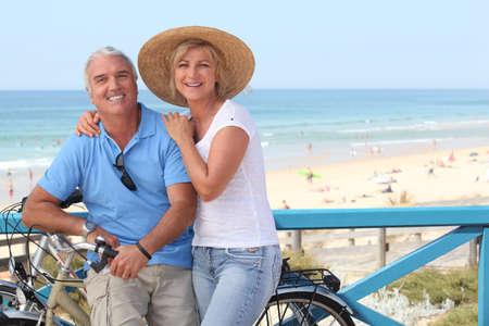 mujeres mayores: Pareja joven con las bicicletas por la playa
