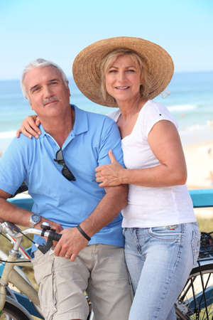 Middle-aged couple enjoying bike ride by the sea photo