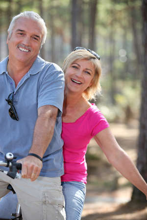 few: man and woman riding a bike in the forest