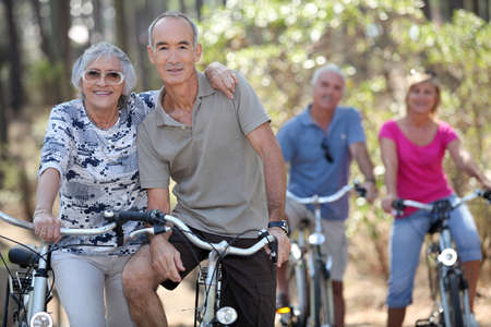 people laughing: Elderly people riding their bikes Stock Photo