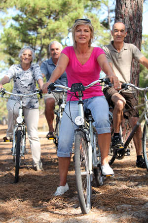 Two middle-aged couples riding bicycles photo