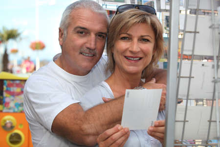 Couple choosing postcard Stock Photo - 14211461