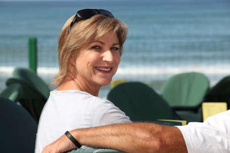 blithe: Mujer sentada en un caf� a orillas del mar