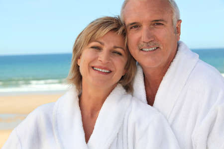 Couple at the beach in bathrobes Imagens