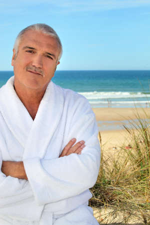 toweling: Middle aged man in a toweling robe by the sea Stock Photo
