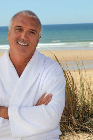 grey haired: Grey haired man in bathing robe stood on beach
