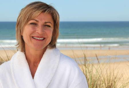 Woman with a bathrobe on the beach Stock Photo - 14211273