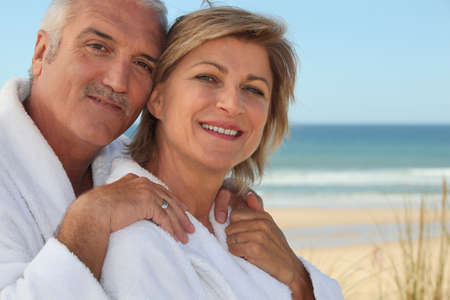 Elderly couple wearing white at the beach photo