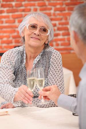 retired couple celebrating anniversary at restaurant photo