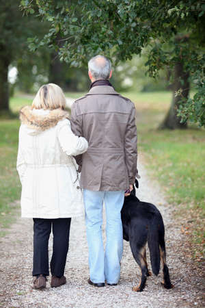 Senior people having a walk with dog photo