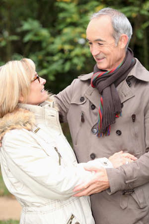couples outdoors: Older couple embracing on a winters stroll