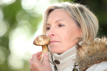olfaction: Woman sniffing a mushroom Stock Photo