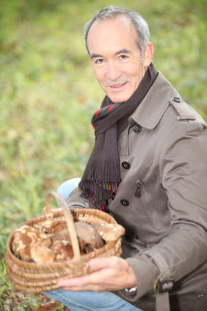 65 years old: Man picking mushrooms in the forest