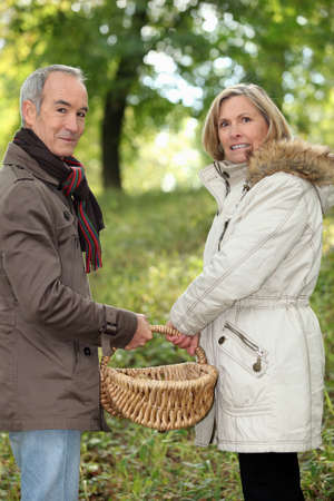 teaching stations: Couple walking through field with basket Stock Photo