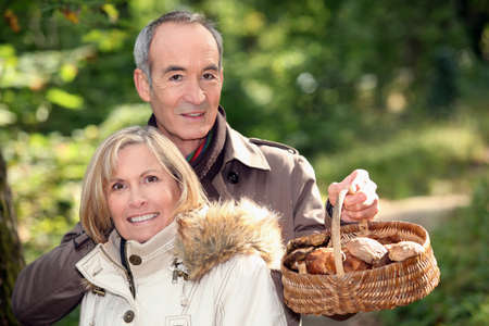 Couple gathering mushrooms in basket photo