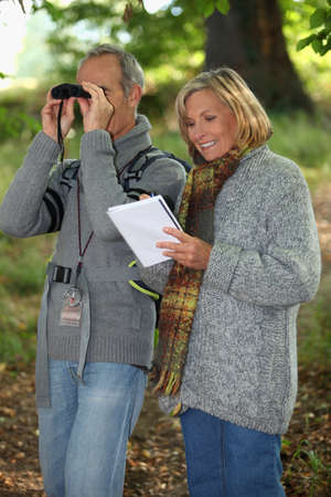 pensioner: Senior woman and senior man watching through binoculars Stock Photo