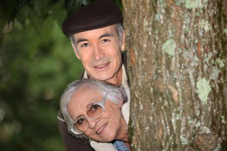 secreted: Elderly couple behind tree