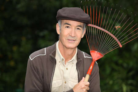 65 years old: 65 years old man wearing brown clothes and holding a rake Stock Photo