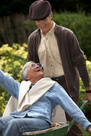 Elderly couple in wheelbarrow Stock Photo - 14203453
