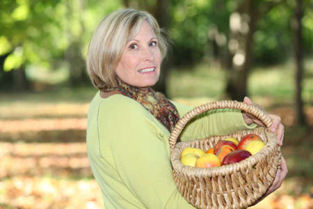 bourgeoisie: mature blonde woman in orchard Stock Photo