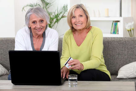 global retirement: Older women using a credit card online Stock Photo