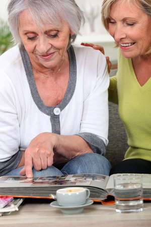 Two women looking through family photo album photo