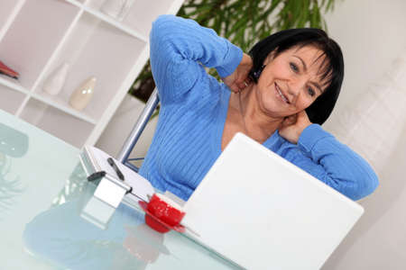 A middle age woman stretching in front of her computer. photo